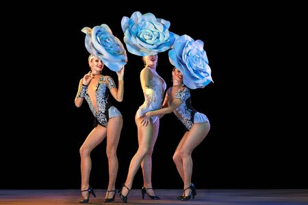 Tender garden. Young female dancers with huge floral hats in neon light on black background. Graceful models, women dancing, posing. Concept of carnival, beauty, motion, blooming, spring fashion. Stock Photo