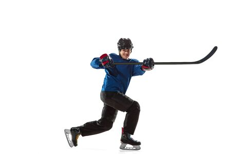 Young female hockey player with the stick on ice court and white background. Sportswoman wearing equipment and helmet training. Concept of sport, healthy lifestyle, motion, action, human emotions. Imagens