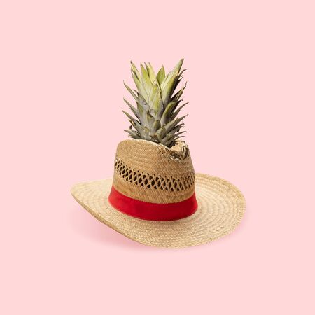 Juicy. Summers hat with pineapple on pastel pink background. Copyspace for your ad. Modern design. Contemporary artwork, collage. Concept of summertime, vacation, resort, mood, beach season.