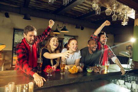 Sportfans jubeln an der Bar, in der Kneipe und trinken Bier, während die Meisterschaft, der Wettbewerb läuft.