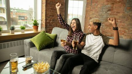 Winning. Excited couple, friends watching sport match, chsmpionship at home. Multiethnic friends, fans cheering for favourite national basketball, tennis, soccer, hockey team. Concept of emotions. Stockfoto