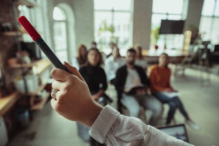 Female muslim speaker giving presentation in hall at workshop. Audience or conference hall. Close up of pointing hand with marker. Conference event, training. Education, diversity, inclusive concept. Stock Photo