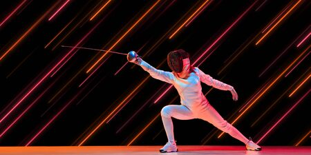 Creative sport and neon lines on dark background, flyer, proposal. Female fencing player training in action and motion. Concept of hobby, healthy lifestyle, youth, action, movement, modern style.