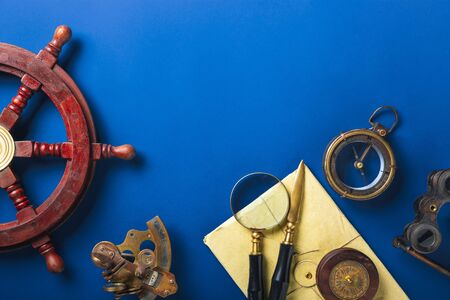 Old fashioned flat lay with retro travel, vacation accessories on blue background. Magnifying glass, compass, steering wheel, envelope, binoculars. Vintage style, steampunk, gaslight concept. Copyspace.