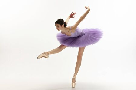 Graceful classic ballerina dancing, posing isolated on white studio background. Bright purple tutu. The grace, artist, movement, action and motion concept. Looks weightless, flexible. Fashion, style. Stock Photo