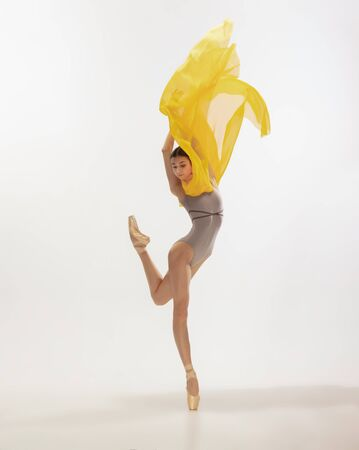 Graceful classic ballerina dancing, posing isolated on white studio background. Bright yellow cloth. The grace, artist, movement, action and motion concept. Looks weightless, flexible. Fashion, style. Stock fotó