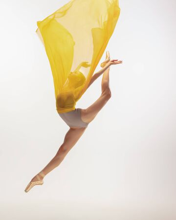 Graceful classic ballerina dancing, posing isolated on white studio background. Bright yellow cloth. The grace, artist, movement, action and motion concept. Looks weightless, flexible. Fashion, style.