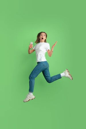 Shocked using phone in jump. Caucasian young womans portrait isolated on green studio background. Beautiful female model in white shirt. Concept of human emotions, facial expression, sales, ad, youth. Reklamní fotografie