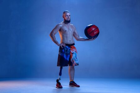 Athlete with disabilities or amputee isolated on blue studio background. Professional male sportsman with leg prosthesis training with ball in neon. Disabled sport and overcoming, wellness concept.