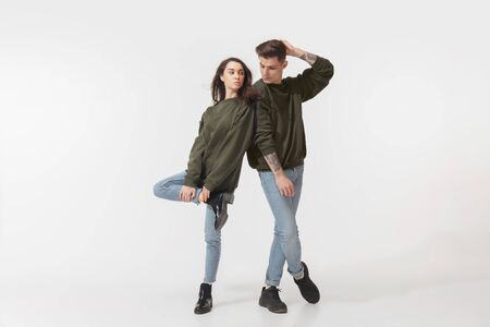 Supporting. Trendy fashionable couple isolated on white studio background. Caucasian woman and man posing in basic minimal unisex clothes. Concept of relations, fashion, beauty, love. Inclusive.