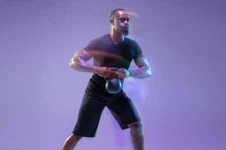 Emotional. Young african-american bodybuilder training over purple background in neon, mixed light. Muscular model with weight. Concept of sport, bodybuilding, healthy lifestyle, motion and action.