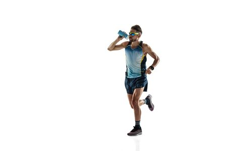 Triathlon male athlete running isolated on white studio background. Caucasian fit jogger, triathlete training wearing sports equipment. Concept of healthy lifestyle, sport, action, motion. Drinks water.