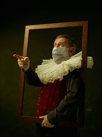 Frame. Senior man as a medieval knight on dark background wearing protective mask against coronavirus. Retro style, comparison of eras concept. Healthcare, prevention spread of pandemic. Stay safe.