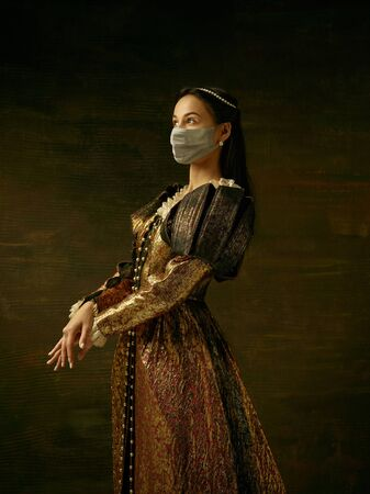 Medieval young woman as a duchess wearing protective mask against coronavirus spread on dark blue background. Concept of comparison of eras, healthcare, medicine and prevention against pandemic.