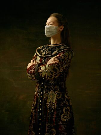 Medieval young woman as a duchess wearing protective mask against coronavirus spread on dark blue background. Concept of comparison of eras, healthcare, medicine and prevention against pandemic. Reklamní fotografie