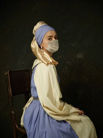 Medieval young woman as a lady with a pearl earring wearing protective face mask against coronavirus spread. Concept of comparison of eras, healthcare and medicine, prevention pandemic flu virus.