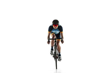 Triathlon male athlete cycle training isolated on white studio background. Caucasian fit triathlete practicing in cycling wearing sports equipment. Concept of healthy lifestyle, sport, action, motion.