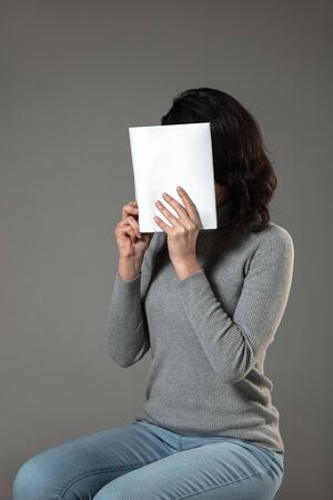 Happy world book and copyright day, read to become someone else - woman covering face with book while reading on grey studio background. Celebrating, education, art, enjoying new characters concept.