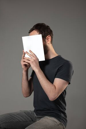 Happy world book and copyright day, read to become someone else - man covering face with book while reading on grey studio background. Celebrating, education, art, enjoying new characters concept. Stock Photo
