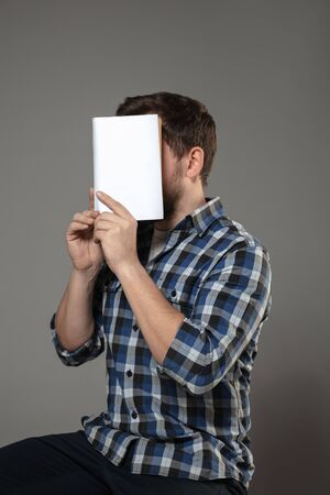 Happy world book and copyright day, read to become someone else - man covering face with book while reading on grey studio background. Celebrating, education, art, enjoying new characters concept.