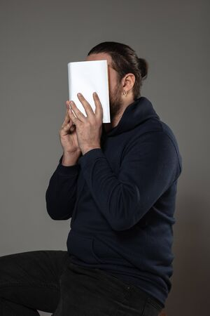 Happy world book and copyright day, read to become someone else - man covering face with book while reading on grey studio background. Celebrating, education, art, enjoying new characters concept. Foto de archivo