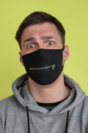Scared eyes. Caucasian mans portrait isolated on yellow studio background. Freaky male model in black face mask. Concept of human emotions, facial expression, sales, ad. Unusual appearance.