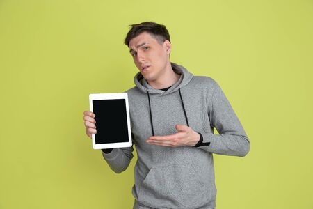 Showing tablet blank screen. Caucasian mans portrait isolated on yellow studio background. Freaky model in casual clothes. Concept of human emotions, facial expression, sales, ad. Unusual appearance. Imagens