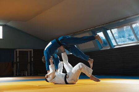 Two young judo caucasian fighters in white and blue kimono with black belts training martial arts in the gym with expression, in action, motion. Practicing fighting skills. Overcoming, reaching target. Archivio Fotografico
