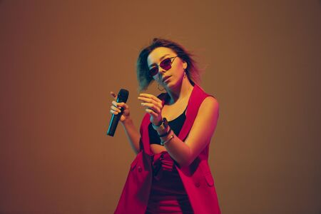 Young caucasian musician, performer singing on gradient background in neon light. Concept of music, hobby, festival. Joyful woman party host, DJ, singer, bands front artist. Colorful portrait.