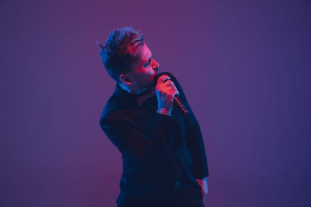 Young caucasian musician, performer singing on gradient purple-blue background in neon light. Concept of music, hobby, festival. Joyful party host, DJ, stand upper, singer. Colorful portrait of artist.