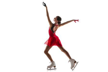 Girl figure skating isolated on white studio backgound with copyspace. Professional practicing and training in action and motion on ice. Graceful and weightless. Concept of movement, sport, beauty. 免版税图像
