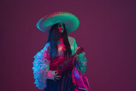 在紫色演播室背景的美妙的cinco de mayo女性舞蹈家在霓虹灯。在传统服装和阔边帽跳舞的美好的女性模型。庆祝,假日,美容和时尚概念。