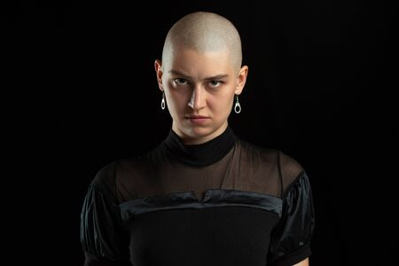Serious, mystic. Monochrome portrait of young caucasian bald woman isolated on black studio background. Beautiful female model. Human emotions, facial expression, sales, ad concept. Youth culture.