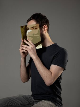 Happy world book day 2020, be safe and read to become someone else - man covering face with book in mask while reading on grey studio background. Celebrating, education, art, protection concept.