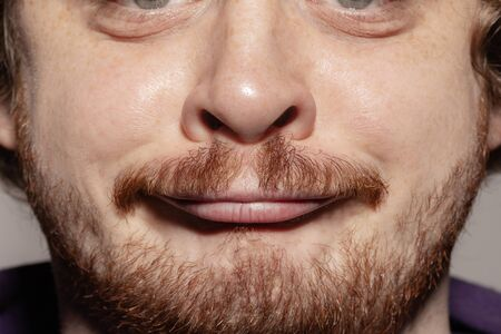 Grimaces. Close up of face of beautiful caucasian young man with redhair beard, focus on mouth. Human emotions, facial expression, cosmetology, body and skin care concept. Well kept skin. Wellbeing.