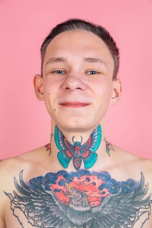 Close up portrait of young man with freaky appearance on pink background. Unusual look with huge tattooes. Doing daily routine. Human emotions, facial expression, sales, ad concept. Youth culture.