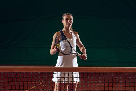 Young caucasian professional sportswoman playing tennis on sport court background. Training, practicing in motion, action. Power and energy. Movement, ad, sport, healthy lifestyle concept. Front view.