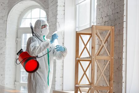 Coronavirus Pandemic. A disinfector in a protective suit and mask sprays disinfectants in house or office. Protection agsinst COVID-19 disease. Prevention of spreding pneumonia virus with surfaces. Reklamní fotografie