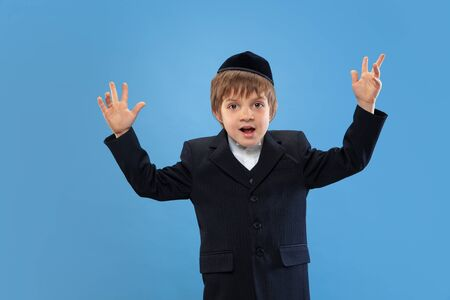Dancing fun. Portrait of a young orthodox jewish boy isolated on blue studio background. Purim, business, festival, holiday, childhood, celebration Pesach or Passover, judaism, religion concept.