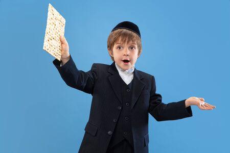 Joyfull eating matzah. Portrait of a young orthodox jewish boy isolated on blue studio background. Purim, business, festival, holiday, childhood, celebration Pesach or Passover, judaism, religion concept.