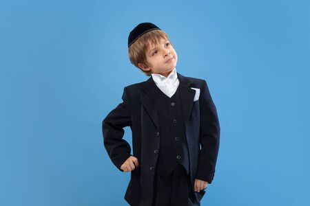 Posing confident, cute. Portrait of a young orthodox jewish boy isolated on blue studio background. Purim, business, festival, holiday, celebration Pesach or Passover, judaism, religion concept. Stock Photo