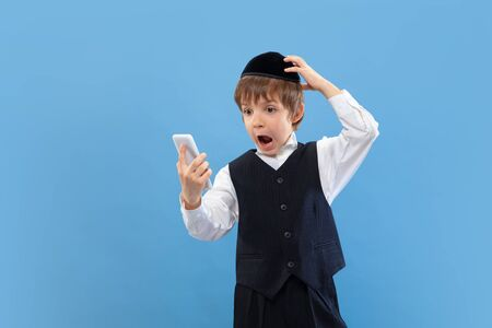 Shocked using phone. Portrait of a young orthodox jewish boy isolated on blue studio background. Purim, business, festival, holiday, childhood, celebration Pesach or Passover, judaism, religion concept.