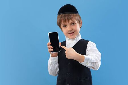 Shows blank phone screen. Portrait of orthodox jewish boy isolated on blue studio background. Purim, business, festival, holiday, childhood, celebration Pesach or Passover, judaism, religion concept. Stock Photo