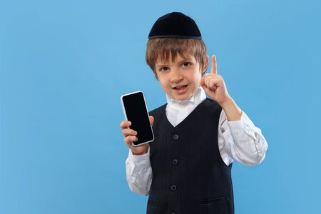 Shows blank phone screen. Portrait of orthodox jewish boy isolated on blue studio background. Purim, business, festival, holiday, childhood, celebration Pesach or Passover, judaism, religion concept.