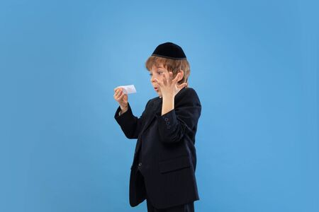 Getting money. Portrait of a young orthodox jewish boy isolated on blue studio background. Purim, business, festival, holiday, childhood, celebration Pesach or Passover, judaism, religion concept.
