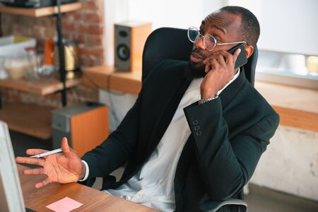 Calling, talking on phone. African-american entrepreneur, businessman working concentrated in office. Looks serios, busy, wearing classic suit. Concept of work, finance, business, success, leadership.