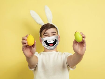 Happy Easter. Portrait of young caucasian boy with emotion on his protective face mask isolated on studio background. Beautiful male model. Human emotions, facial expression, sales, ad concept.