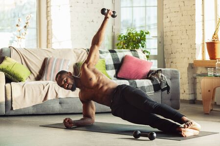 African-american man teaching at home online courses of fitness, aerobic, sporty lifestyle while being quarantine. Getting active while isolated, wellness, movement concept. Training with weights.