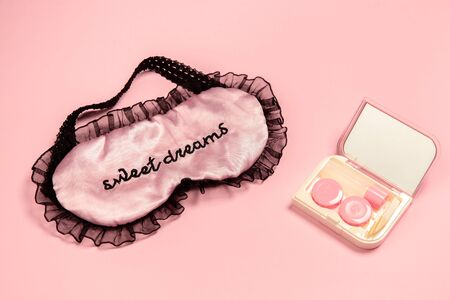 Lenses in case with mirror and sleep mask. Monochrome stylish and trendy composition in pink color on studio background. Top view, flat lay. Pure beauty of usual things around. Copyspace for ad.