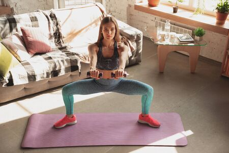 Young woman teaching at home online courses of fitness, aerobic, sporty lifestyle while quarantine. Getting active while isolated, wellness, movement concept. Exercises with weights, balance.